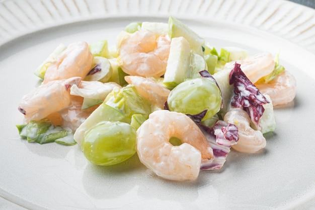 健康食品のコンセプト、ダイエットサラダプレート。灰色のテーブルの上に、エビまたはエビのセット、ソースアップルとブドウの新鮮なシーフードサラダ