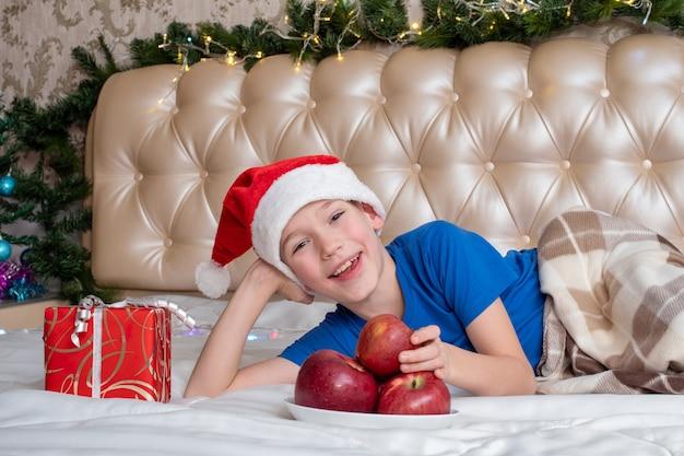 クリスマスのための健康食品のコンセプト。サンタの帽子で陽気なかわいい白人の男の子