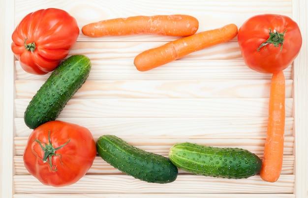 健康食品のコンセプトです。野菜のフレーム。トマトクールドブフ、キュウリ、ニンジンの木製の背景