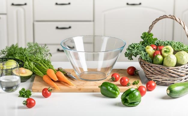 健康食品のコンセプト。キッチンのまな板の白いテーブルに新鮮な野菜。