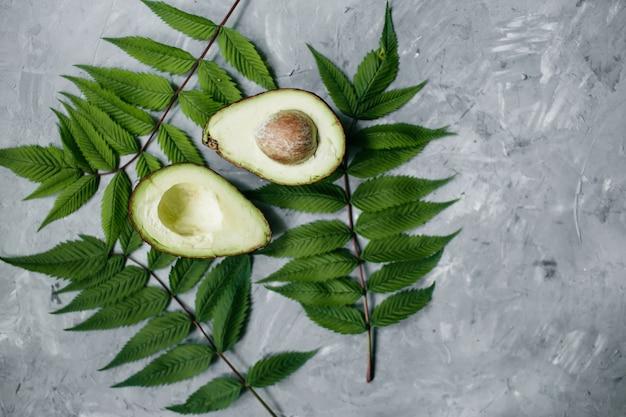 健康食品のコンセプト。灰色の背景に緑の葉とアボカド。フラットレイ、上面図、コピースペース。