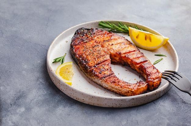 健康食品のコンセプトです。灰色の石の背景に白い皿にローズマリーソーバーレモン添えサーモンステーキのグリル。 copyspaceとflatlay。オメガのコンセプト