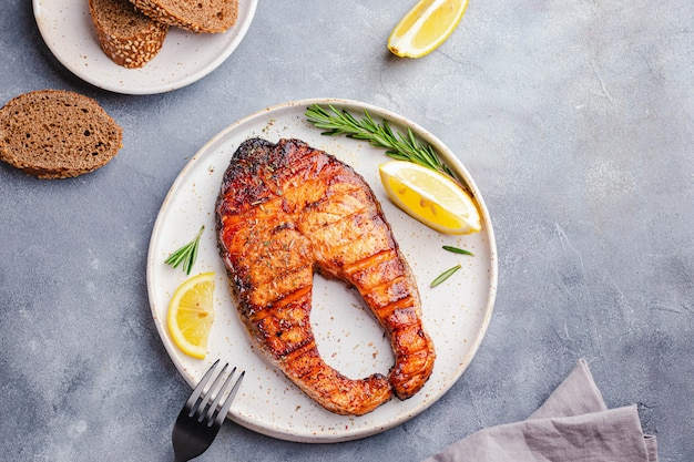 健康食品のコンセプトです。サーモンステーキのグリルレモン、ローズマリー、灰色の石の白い皿の上