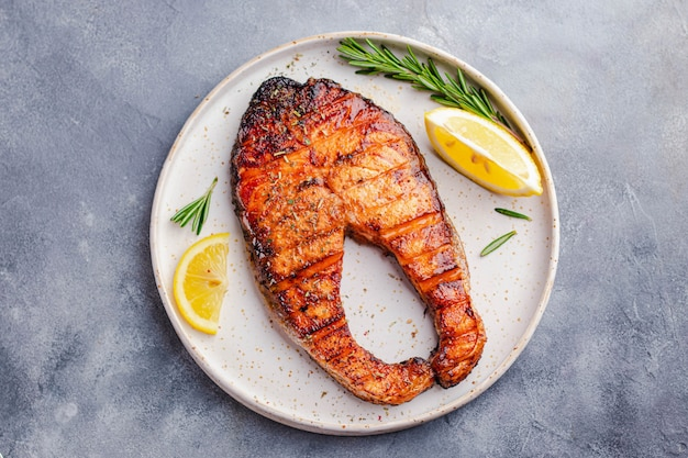 Healthy food concept. grilled salmon steak with lemon, rosemary served on white plate on gray stone