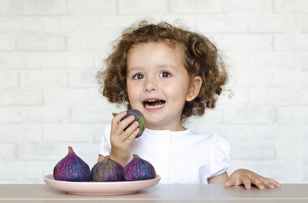 健康食品のコンセプトです。新鮮なイチジクを食べて楽しんで幸せな子。女の子は適切なスナックをお楽しみください。子供は果実や果物が大好きです。秋の収穫