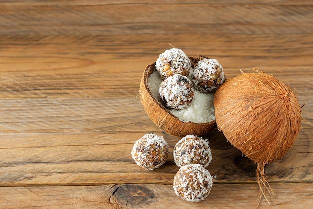 건강 식품 개념입니다. 나무 배경에 코코넛 껍질에 홈메이드 코코넛 에너지 볼.