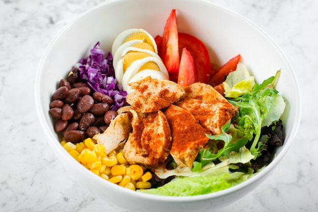 Healthy food concept. lunch bowl with chicken, egg, tomatoes, lettuce, corn, red beans, red cabbage. clean food and dieting nutrition concept. close-up