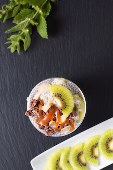 Healthy food concept organic chia pudding with kiwi fruit and chocolate muesli with copy space