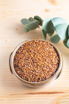 Healthy food concept organic flax seeds in ceramic bolw on wooden board with copy space