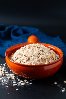 Healthy food concept organic whole-grain rolled oats in orange bowl with blue napkins on black slate stone