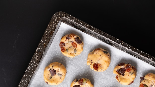 Healthy food concept raw dougn of homemade trail mix organic whole grains energy cookies in baking pan with copy space