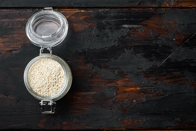 건강 식품 개념. 오래 된 어두운 나무 테이블에 유리 항아리에 참 깨 세트