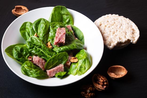 健康食品のコンセプトコピースペース付きの黒いスレート石板に白いセラミック皿にフランスのpresskopfとほうれん草のサラダ