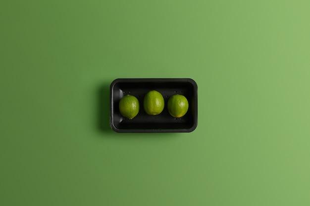 Concetto di cibo sano. tre limette succose mature confezionate su vassoio isolato su sfondo verde vivido. frutta intera acida degli agrumi per la vendita nel mercato. ingrediente per preparare limonata fresca o cocktail