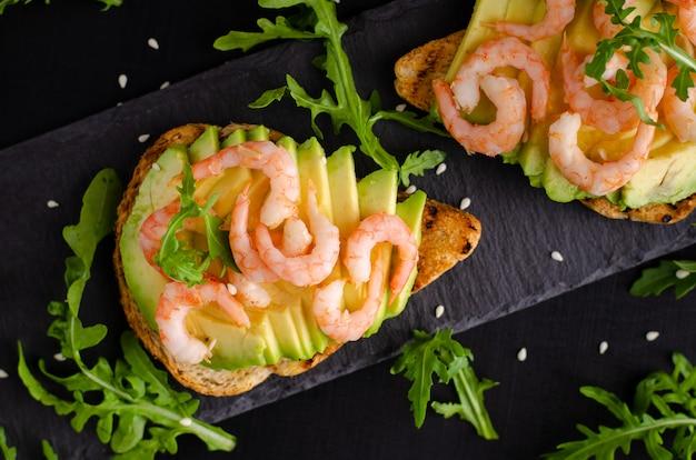 Концепция здорового питания. тосты с авокадо, креветками и рукколой. вид сверху, плоская планировка