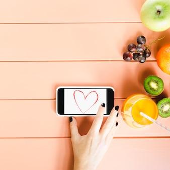 Concetto di cibo sano con smartphone e frutta
