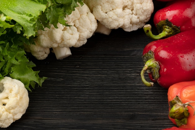 Healthy food concept with vegetables on a dark wooden background with top view and copy space