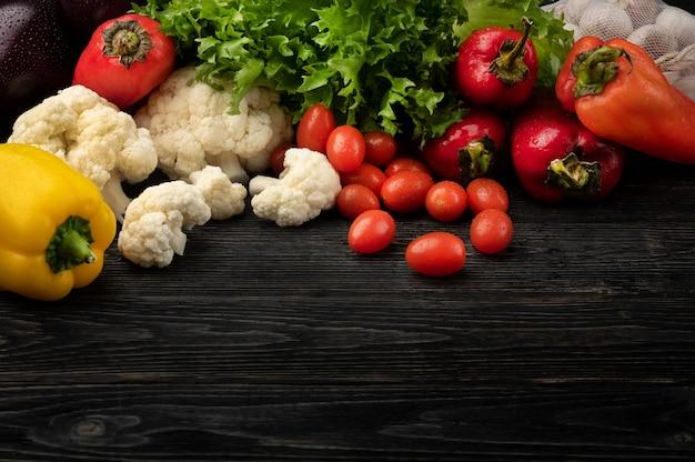 トップビューとコピースペースと暗い木製の背景に野菜と健康食品のコンセプト