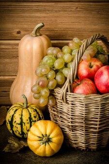 건강한 음식 내용, 호박 호박의 정물, 미니 호박, 녹색 및 노란색 포도가 있는 고리버들 바구니, 빨간 사과, 어두운 탁자, 나무 배경