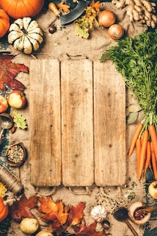 Healthy food cooking background. fresh garden carrots, onions, pumpkins, ginger and spices on rustic wood, top view, copy space