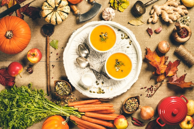 Healthy food cooking background. vegetable ingredients and homemade soup. fresh garden carrots, onions, pumpkins, ginger and spices on rustic wood, top view, copy space