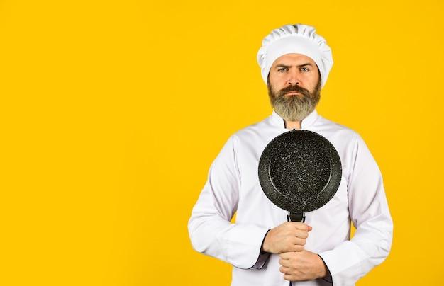 Приготовление здоровой пищи. готовим вкусное блюдо. бородатый мужчина держит сковороду. готовим в горшочке. для приготовления еды. бородатый мужчина готовит на кухне. кулинария и кухня. кухонная утварь. копировать пространство.