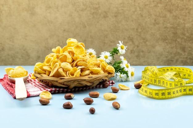 カモミールの花、センチメートルテープ、青の木のスプーンと赤いタオルのウィッカープレートの健康食品コーンフレーク