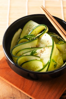 Healthy food  cucumber salad with soy sauce and sesame dressing in black bowl