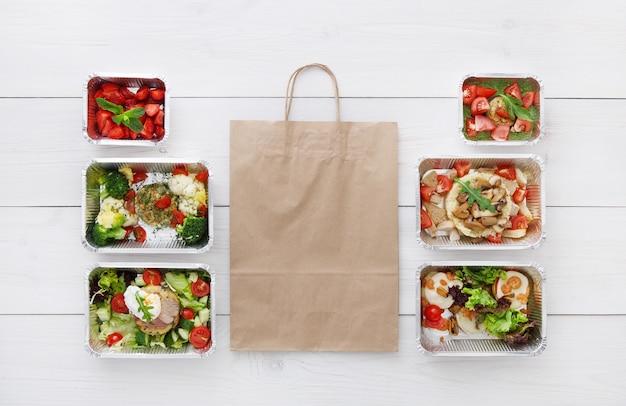 건강한 음식 배달, 매일 식사 및 간식. 호일 상자와 갈색 종이 포장에 영양, 야채, 고기 및 과일. 평면도, 평면 복사 공간 흰색 나무에 누워