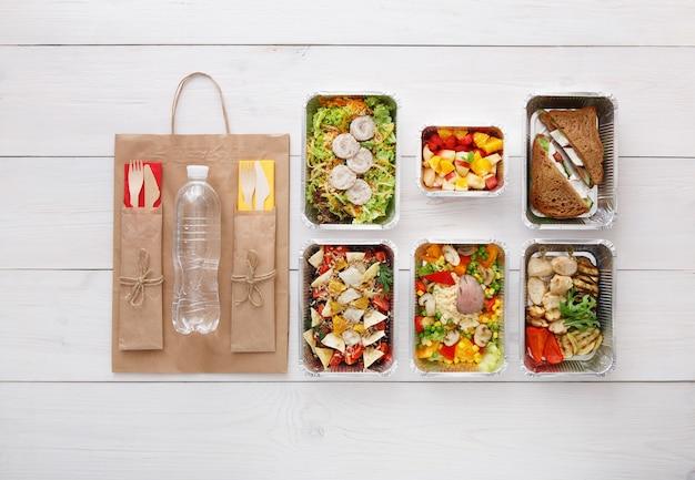 건강한 음식 배달, 매일 식사 및 간식. 영양, 야채, 고기, 물병 및 과일을 호일 상자와 갈색 종이 패키지에 담았습니다. 평면도, 평면 복사 공간 흰색 나무에 누워