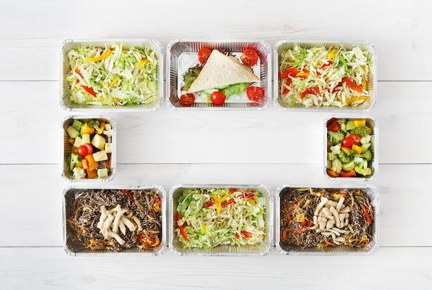 Доставка здорового питания, суточный рацион. уберите натуральные экологически чистые продукты в рамке из фольги. вид сверху, плоская планировка с копией пространства на белом дереве
