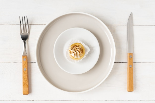 Healthy food and diet concept. small dessert on a big plate served with fork and knife on white table.