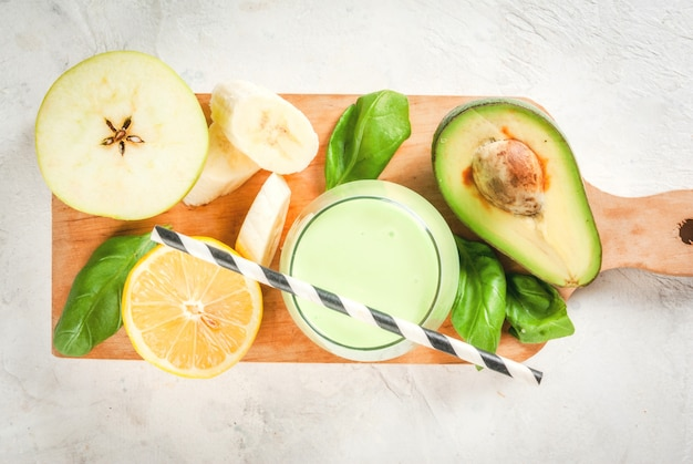 Healthy food. dietary breakfast or snack. green smoothies from yoghurt, avocado, banana, apple, spinach and lemon. on white concrete stone table, with ingredients.  top view