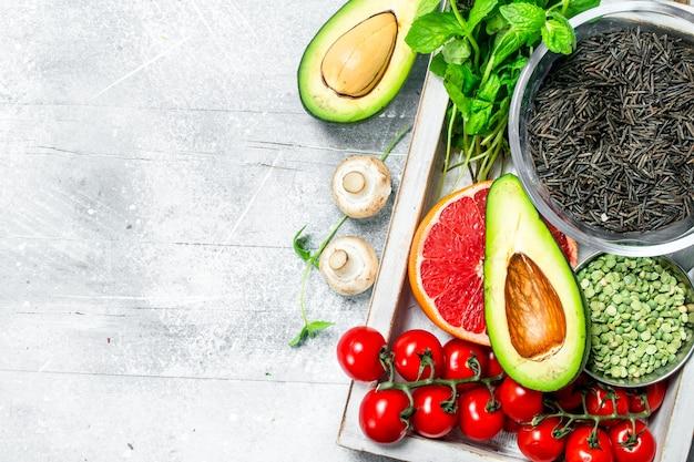 健康食品。木製の箱に黒米とさまざまな有機果物や野菜。素朴なテーブルの上。