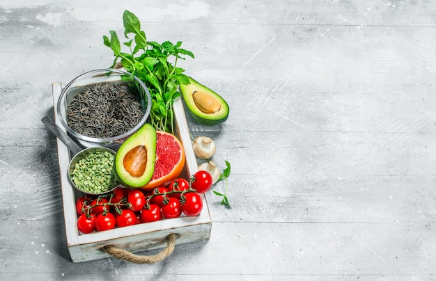 健康食品。木製の箱に黒米とさまざまな有機果物や野菜。素朴に。