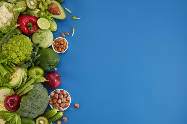 Healthy food dish on blue background. healthful set including vegetables and fruits. grape, apple, kiwi, pepper, lime, cabbage, zucchini, grapefruit, nuts. proper nutrition or vegetarian menu.