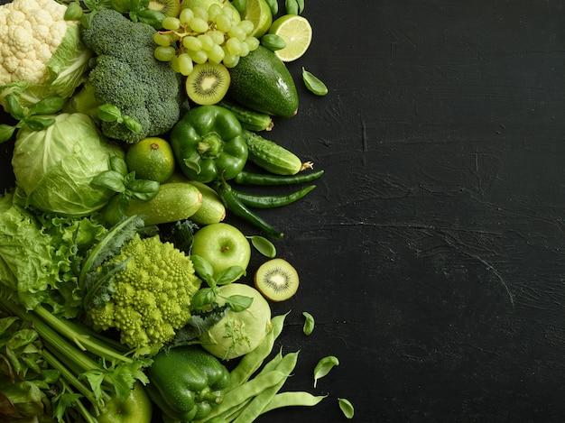 검은 돌 배경에 건강 식품 요리입니다. 야채와 과일을 포함한 건강에 좋은 세트. 포도, 사과, 키위, 후추, 라임, 양배추, 호박, 자몽. 적절한 영양 또는 채식 메뉴.