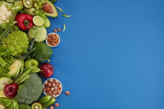 Блюдо здорового питания на синем фоне. здоровый набор, включая овощи и фрукты. виноград, яблоко, киви, перец, лайм, капуста, кабачки, грейпфрут, орехи. правильное питание или вегетарианское меню.