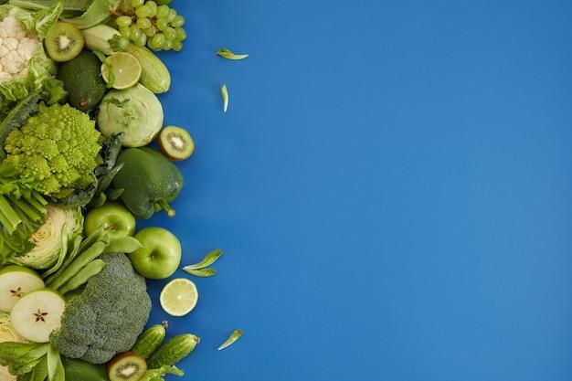Блюдо здорового питания на синем фоне. здоровый набор, включая овощи и фрукты. виноград, яблоко, киви, перец, лайм, капуста, кабачки, грейпфрут. правильное питание или вегетарианское меню.