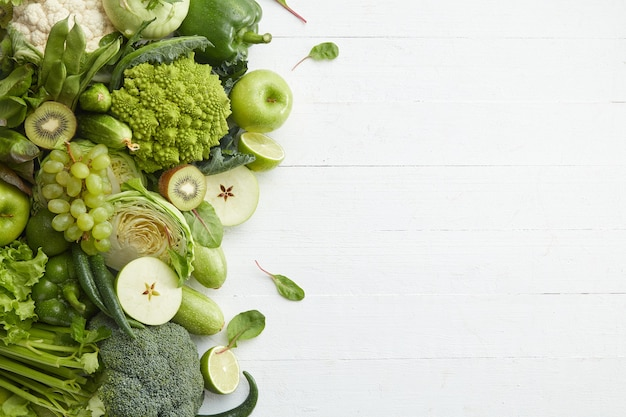 흰색 바탕에 건강 식품 접시입니다. 야채와 과일을 포함한 건강 세트. 포도, 사과, 키위, 후추, 라임, 양배추, 호박, 자몽. 적절한 영양 또는 채식 메뉴.