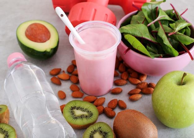 Здоровая еда, гантели и бутылка с водой