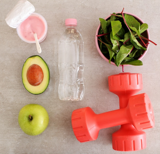 Healthy food, dumbbells and water bottle