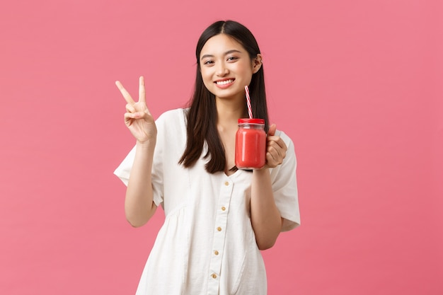 Cibo sano, emozioni e concetto di stile di vita estivo. felice bella ragazza asiatica in abito bianco, che mostra il segno di pace kawaii e beve frullato da vetro e paglia.