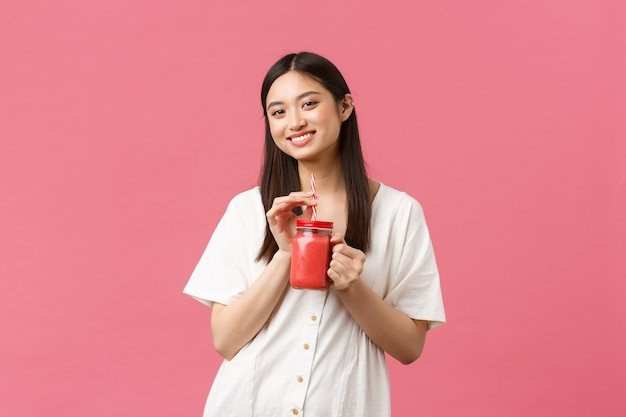Healthy food, emotions and summer lifestyle concept. smiling good-looking fit asian girl taking care of body, drinking fresh smoothie from glass and gazing camera satisfied, pink background.