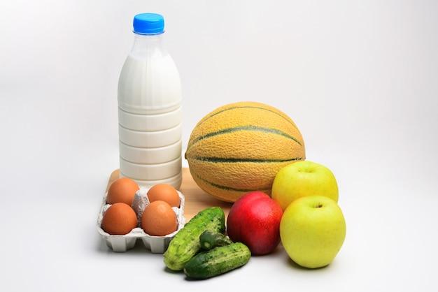 健康食品魚野菜果物牛乳と白い背景の上の卵