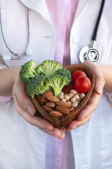 心臓のための健康食品、ダイエットの概念。野菜、ナッツ、ひよこ豆のボウルを保持している医師