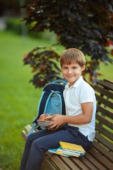 Здоровое питание для школьника. милый мальчик ест фрукты на открытом воздухе возле школы.
