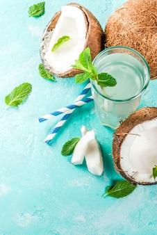 健康食品 。ココナッツ、アイスキューブ、ミント、ライトブルー、トップビューで新鮮な有機ココナッツ水