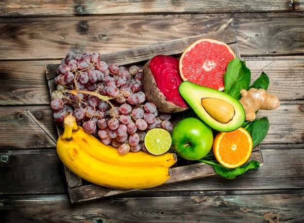 건강한 음식. 오래 된 상자에 신선한 유기농 과일과 야채. 나무 배경.