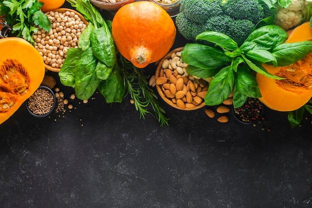야채, 단백질이 풍부한 곡물로 만든 건강식. 브로콜리, 호박, 병아리콩, 아몬드, 검정색 배경에 다양한 채소. 배너, 복사 공간